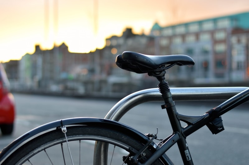 The backend of a macro black bicycle parked against a steel rail in the city