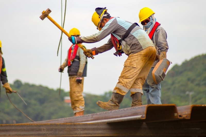 construction-worker-on-roof-swinging-hammer