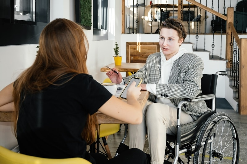woman-employee-in-wheelchair-talking-with-colleague